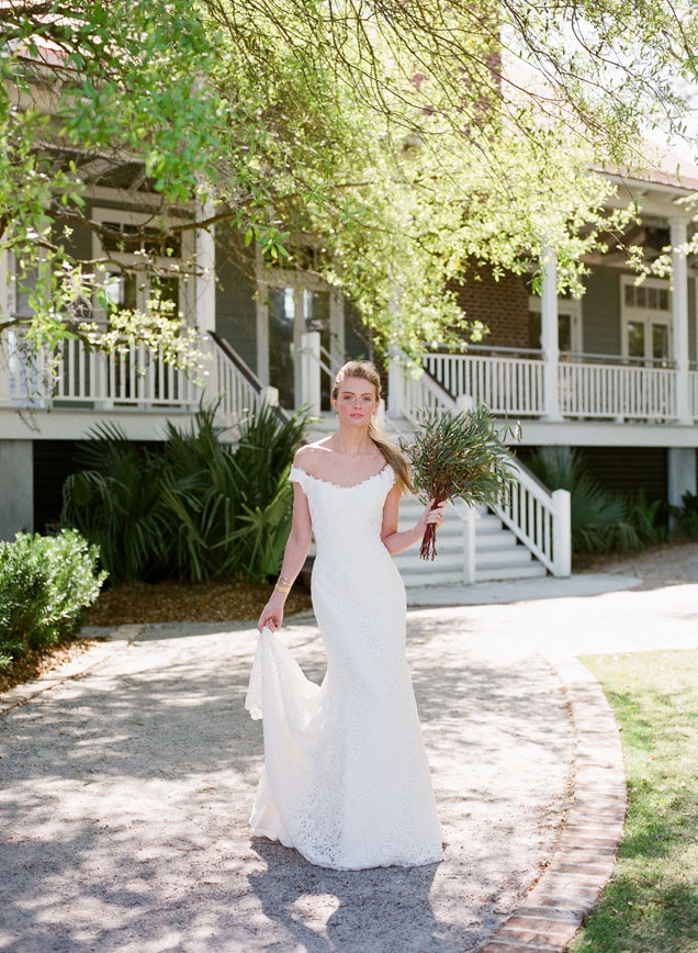 "Modern Trousseau's ""Hepburn"" guipure lace gown available from Modern Trousseau flagship stores in Charleston, Savannah, and Nashville. Gold and diamond earrings and ring from Roberto Coin. Christina Jervey cuffs from Gwynn's of Mount Pleasant. Bouquet by Fox Events"