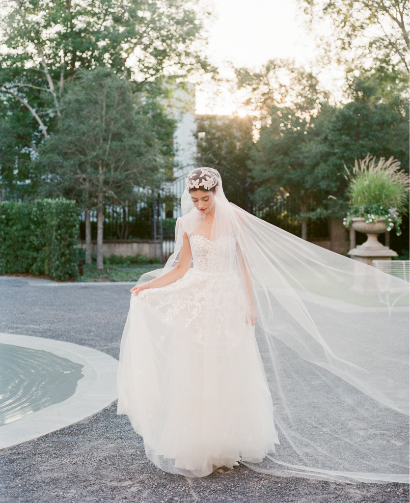 "Mira Zwillinger's ""Charlie"" A-line tulle silk gown with appliqués from Betty Bridal Atelier. Untamed Petals' ""Berlin"" Juliet cap veil with beading from Lovely. Kendra Scott's ""Abigail"" platinum bracelet from Kiawah Fine Jewelry. (Photo by Corbin Gurkin)"