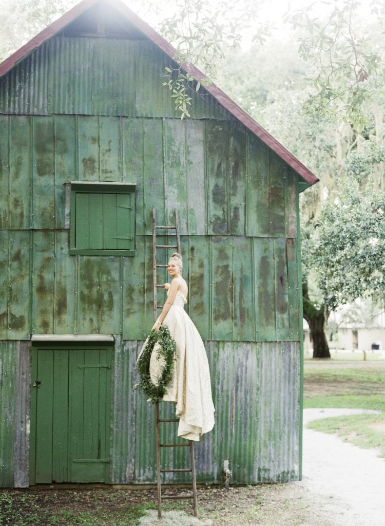 """Modern Trousseau's """"Pride"""" gold brocade high-low gown from Modern Trousseau Charleston. Ladder from Page's Thieves Market. Photograph by Corbin Gurkin."""