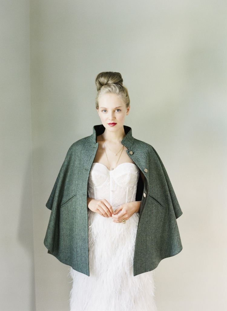 """Lela Rose's """"The Dusk"""" gown with corseted  bodice and ostrich feather skirt (shown without detachable tulle overlay) from Maddison Row. T.ba's tweed cape; Jorge Morales' triple-strand stone necklace; and Leslie Francesca Designs' ring, all from Out of Hand. Photograph by Corbin Gurkin."""