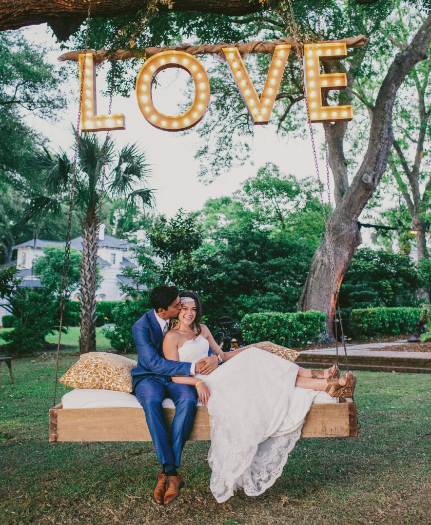 Photograph by Hyer Images at Lowndes Grove Plantation. Swing by Ooh! Events. Love sign by Loluma. Bride's attire by Marchesa (gown); Doloris Petunia (hair accessory).