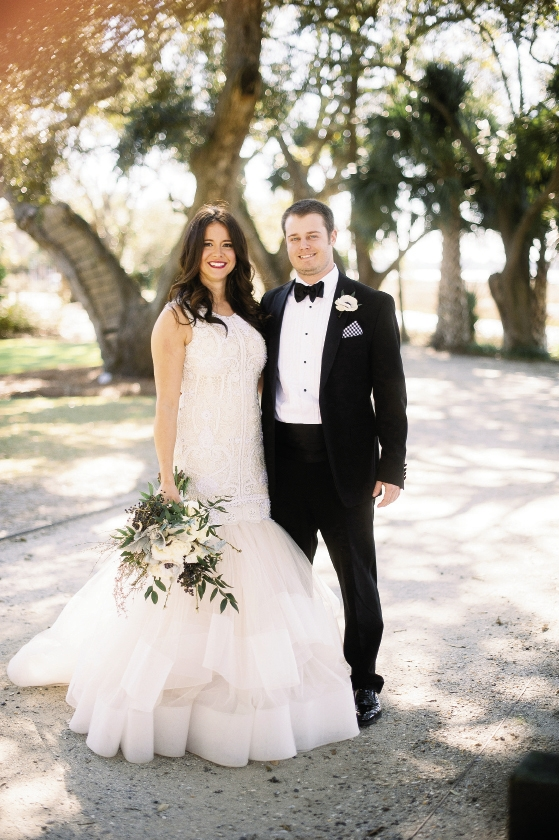 """""""I'm a no-fuss kind of girl who grew up in a large family of boys,"""" says Stephanie, explaining her low-key beauty on the glamorous day. """"It wouldn't have felt right to be made up in a way that wasn't me."""" Bride's gown by Lazaro (available locally at Gown Boutique of Charleston). Florals by Stems Floral Design by Jonie Larosee. Image by Timwill Photography at Lowndes Grove Plantation."""