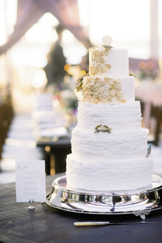 The five-tier cake crafted by Patrick Properties Hospitality Group was adorned with shimmering sugar pearls, tiny blue crabs, and oyster shells as an ode to the couple's love of seafood.  Cake by Patrick Properties Hospitality Group. Image by Timwill Photography.