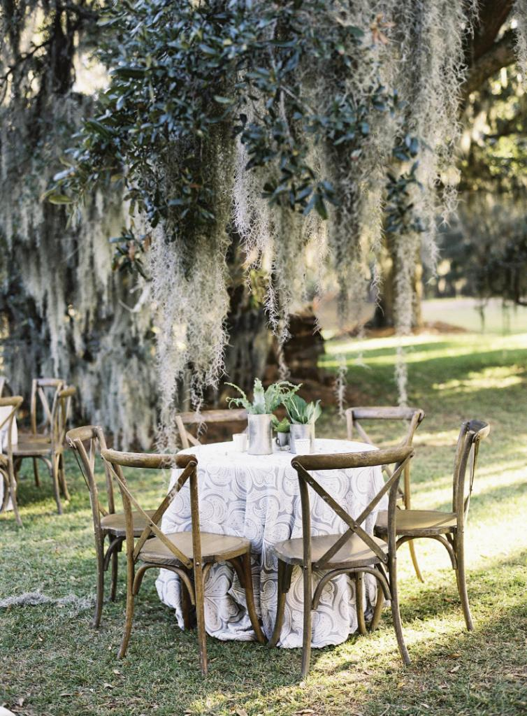 """""""I am definitely a 'no frills' girl and John is a Southern outdoorsman in the truest form,"""" says bride Hollis, who worked with designer Calder Clark to pick a palette lifted from the Lowcountry landscape. Here, gray paisley linens dressed tablescapes topped with greens.  Tables and chairs by Snyder Events. Linens by La Tavola. Florals by Blossoms Events. Photograph by Tec Petaja."""