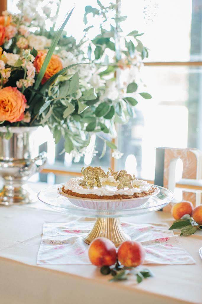 Go Symbolic: In homage to their Thai  honeymoon (and visit to an elephant sanctuary there), pachyderms topped the wedding pie. Peaches gave sweet (and edible) style to tabletops, and home  garden clippings filled out  arrangements of grocery  store blooms.