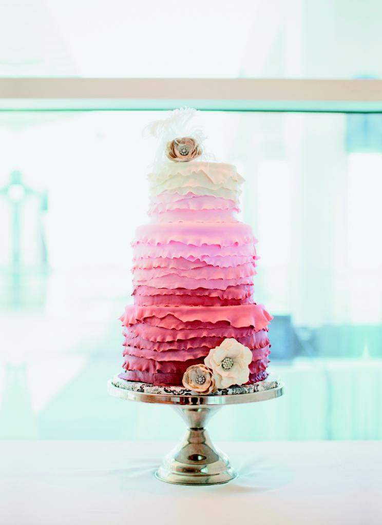 SHADES OF SWEET: Sunny Park Cakes dressed the ombré confection in ruffles and sugar paste flowers to mimic the bodice design and rhinestone belt of Ruth's gown. Wrapping the cake plate in fabric added a colorful touch of pattern to the mix.
