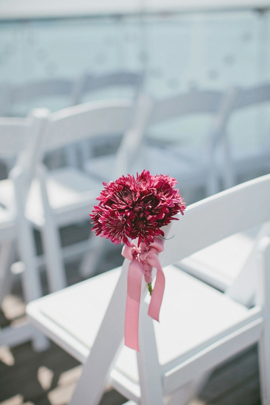 PRETTY IN PINK: Magenta mums tied with light pink ribbons added a splash of color along the aisle.