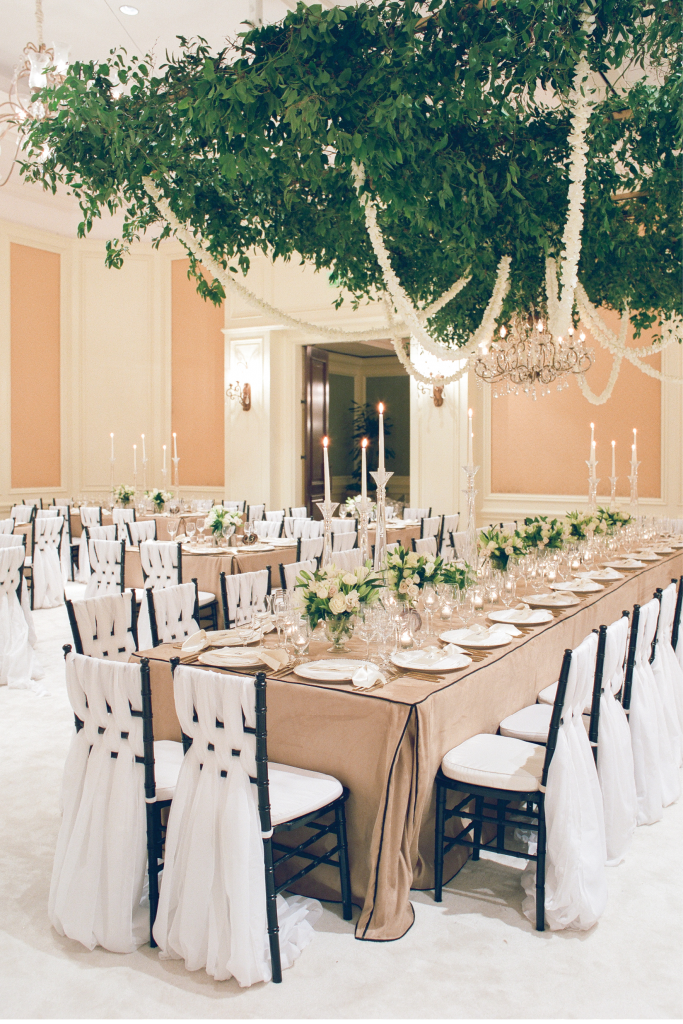 Guests dined under a verdant installation of lush greens and garlands of hand-strung orchids. Chiavari chairs swagged with gauzy fabrics (a signature Tara move), slender crystal candlesticks of varying heights, and custom-made ebony-piped table linens completed the opulent setting.   <i>Photograph by Corbin Gurkin</i>