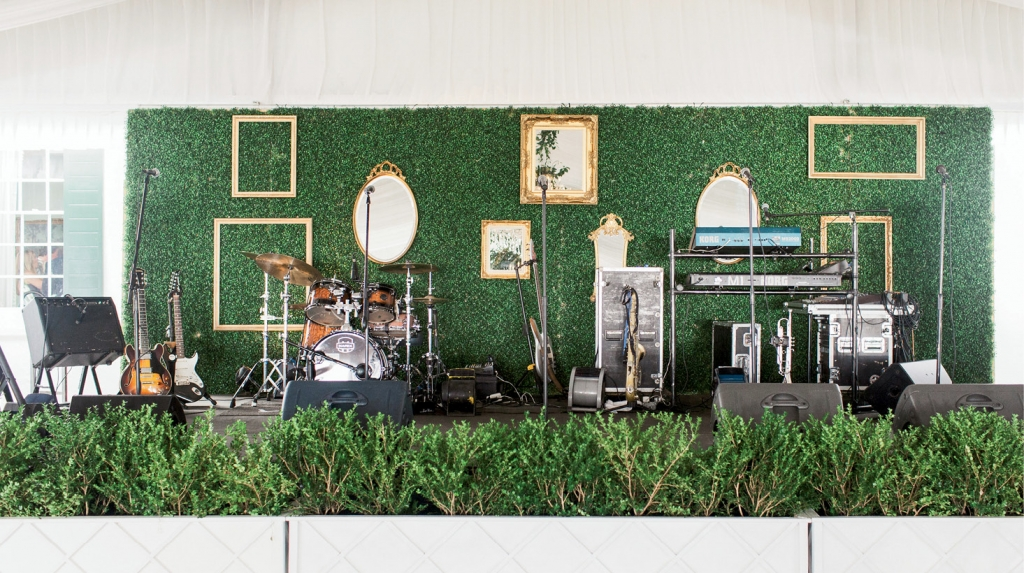 The bandstand backdrop was covered in boxwood greenery and dressed gallery-style with gold mirrors and frames.   <i>Photograph by Gayle Brooker</i>