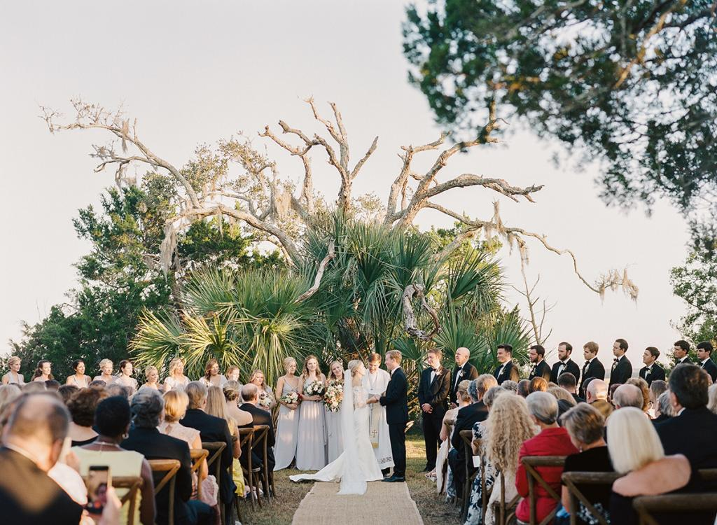 """Anna says her wedding designer Blake was """"the planning genius"""" who found a location for their vows that met all the couple's requirements: amazing views of the Wadmalaw marsh; room for hundreds of guests; and high ground that wouldn't flood, even though the fading day saw a full moon and flood tide."""