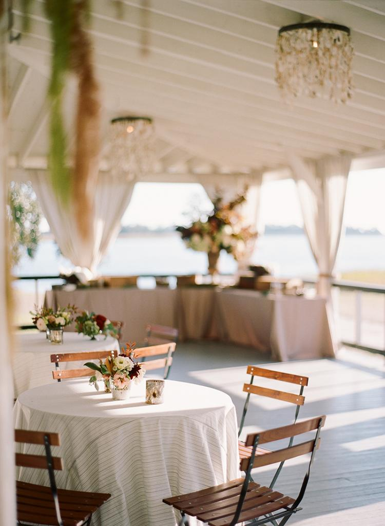 """""""The bride and groom were raised in Charleston and they embody every aspect of the city's character,"""" says planner Blake Sams, """"so the vibe of the day was quintessential Lowcountry—beautiful without being flashy."""" The aesthetic, he says, """"was restrained and timeless, slightly handsome with soft details."""" The way the yacht club's deep porch was styled epitomized just that."""