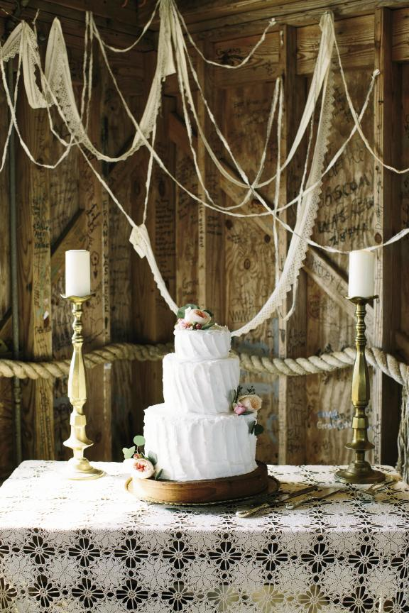Amelia flanked her mother's pound cake with her grandmother's brass candlesticks and draped heirloom lace remnants to sync with the crocheted tablecloth that belonged to her groom's great-grandparents. Cake by bride's mother. Wedding design by bride. Image by Susan Dean Photography at Bowens Island Restaurant.