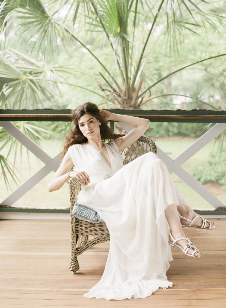 """Jenny Packham's """"Aria"""" gown with blouson top from White on Daniel Island. Blue druzy stone earrings from Out of Hand. Mikal Winn  Designs' brass cuff with blue Swarovski crystal from Out of Hand. """"Reinelle"""" sandal from ALDO. Bar Harbor wicker chair and cushion from Ooh! Events."""