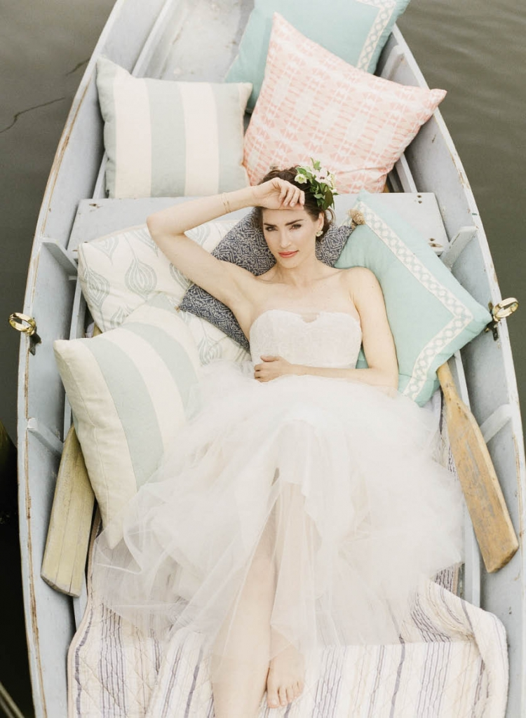 """Christos' """"Lina"""" point d'esprit tulle ball gown from Maddison Row. Kendra Scott's """"Carmella"""" multi-stone earrings from Bella Bridesmaids. Urchin cuff bracelets from Croghan's Jewel Box. Pillows from Ooh! Events and Rockville Retreat. Florals from Out of the Garden. Wooden dinghy  from Lowcountry  Maritime Society."""