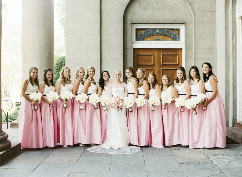 """There is nothing more feminine than a bridesmaid,"" says the bride, who chose LulaKate little white dresses with custom overskirts.  Bride's gown by Amsale (available locally at White on Daniel Island). Bridesmaids' dresses by LulaKate. Florals by Tara Guerard Soiree. Photograph by Corbin Gurkin."