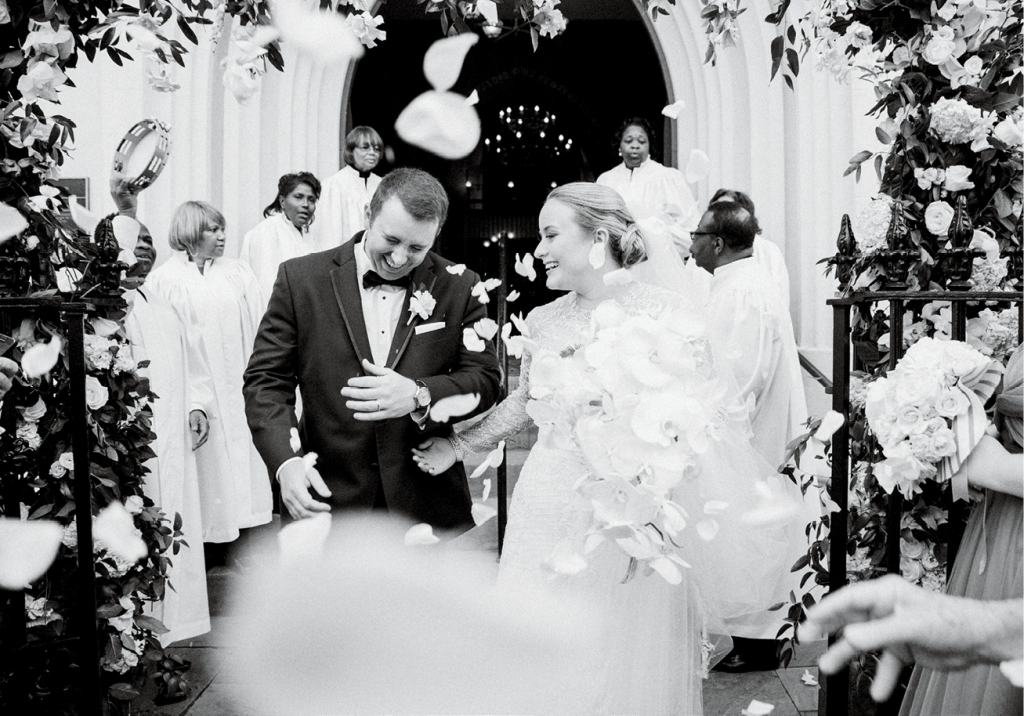 As the newlyweds departed the church, Voices of Deliverance sang them off while guests showered them with rose petals. (Photo by Corbin Gurkin)
