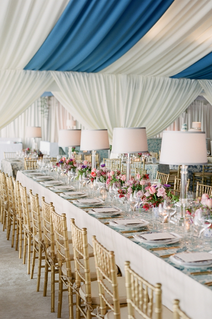 "When the couple selected French Blue as their central color, Tara wondered, ""Everyone loves a blue-and white-wedding, but how can we make it stand out?"" Mix-and-match fabrics did the trick. Tables were dressed in a mélange of custom-made linens in blue-hued florals, patterns that offset the bold ceiling draping. The final touch? Sheer white curtains around the perimeters.  (Photo by Corbin Gurkin)"