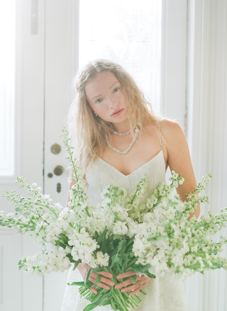 "Lela Rose's ""The Desert"" floral fil coupé gown from Maddison Row. Swarovski crystal and milkstone earrings from Gown Boutique of Charleston. Colibri Collections chalcedony necklace from RTW. Hybrid delphinium and stock flowers from Tiger Lily Weddings. <i>Photograph by Corbin Gurkin</i>"