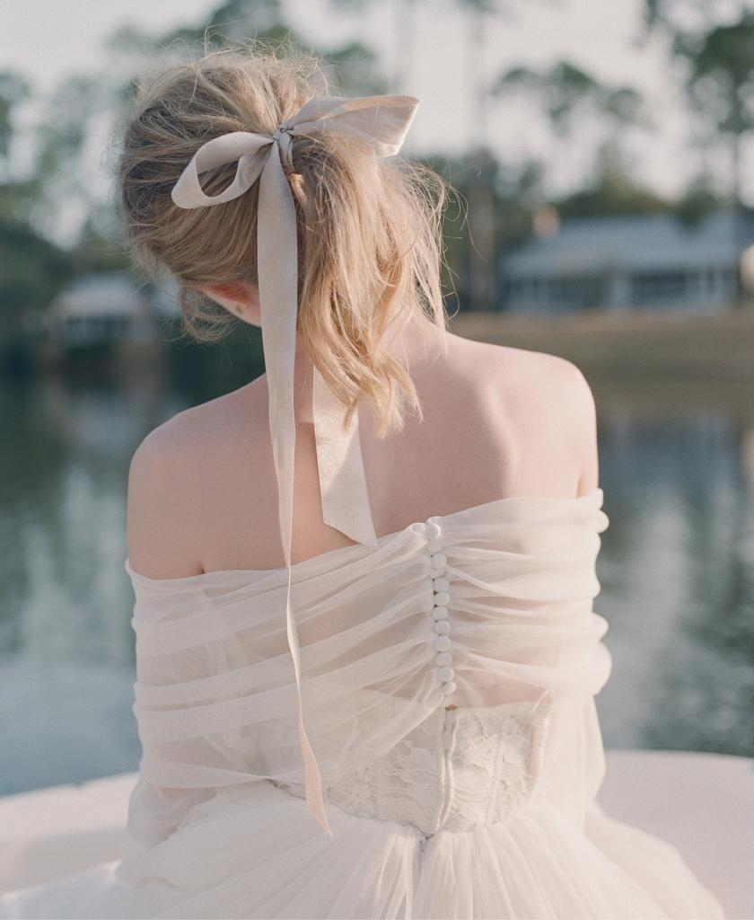 """Silk Chantilly lace and tulle """"Bordeaux"""" gown with removable capelet, both from Emily Kotarski Bridal. Topaz earrings from Gold Creations."""