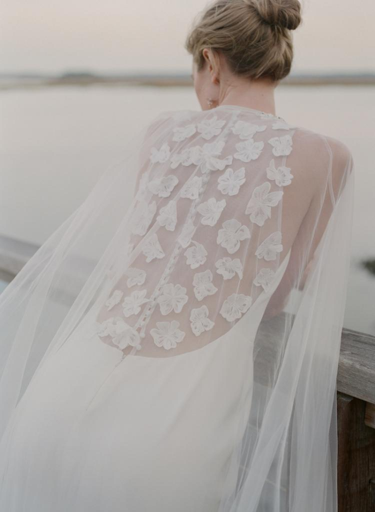 """Lela Rose's silk crepe """"The Notting Hill"""" gown from Maddison Row. Allure's tulle cape with beading from Verità. A Bridal Boutique. Ted Muehling's pearl hoop earrings from RTW."""