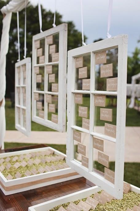 "CLEAR AS DAY: Engaging Events adhered escort cards to vintage window panes for an open, airy look. Below, they placed cards atop green split peas. ""We use these boxes often to display escort envelopes using different mediums depending on the weddings' colors and design,"" says Jessi Martin of Engaging Events.  In this case, it looked rustic, chic, and organic"""