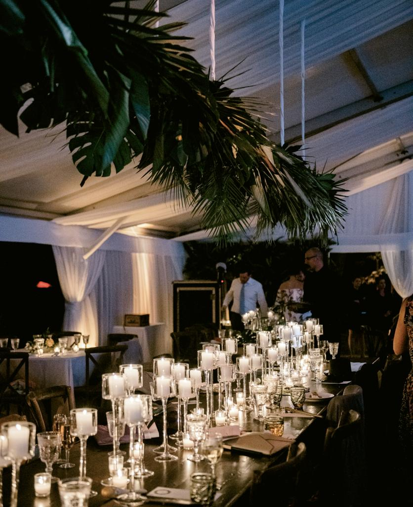 A peek at Lucy's wedding  Pinterest board (@LDietch) tells the tale of what inspired the couple's reception. Pin after pin populated with tropical installations and accents led to a tent dressed in leaves—Monstera, caladium, areca, and hosta—fern fronds, and more. Saved images of candlelight tabletops on her board evoke a club-slash-restaurant vibe while strands of café lights twinkle in merriment.