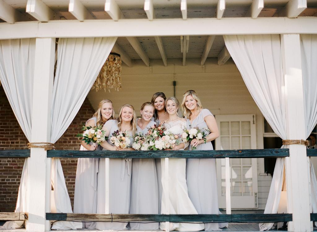 """""""It was one of my favorite moments of the day—to have that time with my bridesmaids before the evening really went into hyperdrive,"""" says Anna, pictured here with her sister, Sarah West, on her far left. """"I really was shocked at the transformation. I knew it would look great but didn't imagine how much I would love it!"""" The oyster shell chandeliers were a love-at-first-sight surprise, she says."""