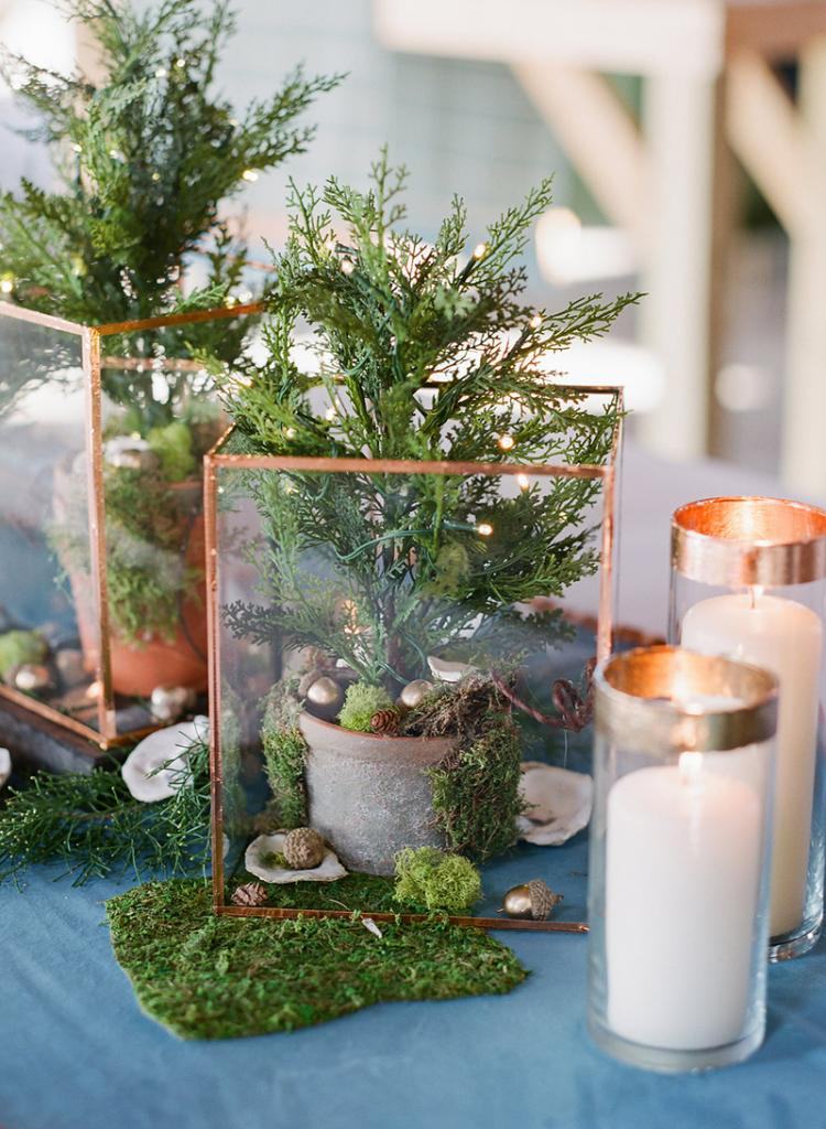 The bride and her mother glued together glass frames trimmed in copper foil to form terrariums they filled with potted firs and flanked with Dollar Tree vases they'd edged in gold