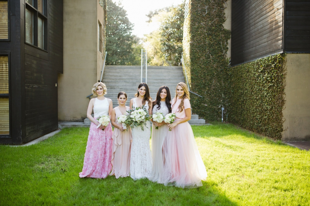 (From left to right) Custom-made bridesmaid ensemble. Bridesmaid's gown from BCBG. Bride's gown by Inbal Dror. Bridesmaid's gown from Needle & Thread. Custom-made bridesmaid ensemble. Florals by Out of the Garden. Hair by Swish. Makeup by Ooh! Beautiful. Image by Clay Austin Photography.