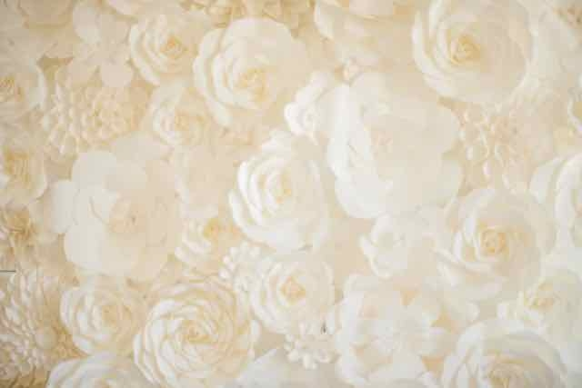 """A paper flower wall provides a stunning backdrop for the head table or lounge area, says Christina. ""I'm building another one for a reception photobooth that will be staged behind a French settee. The flowers can be used again, or the panels can go into the couple's home."""