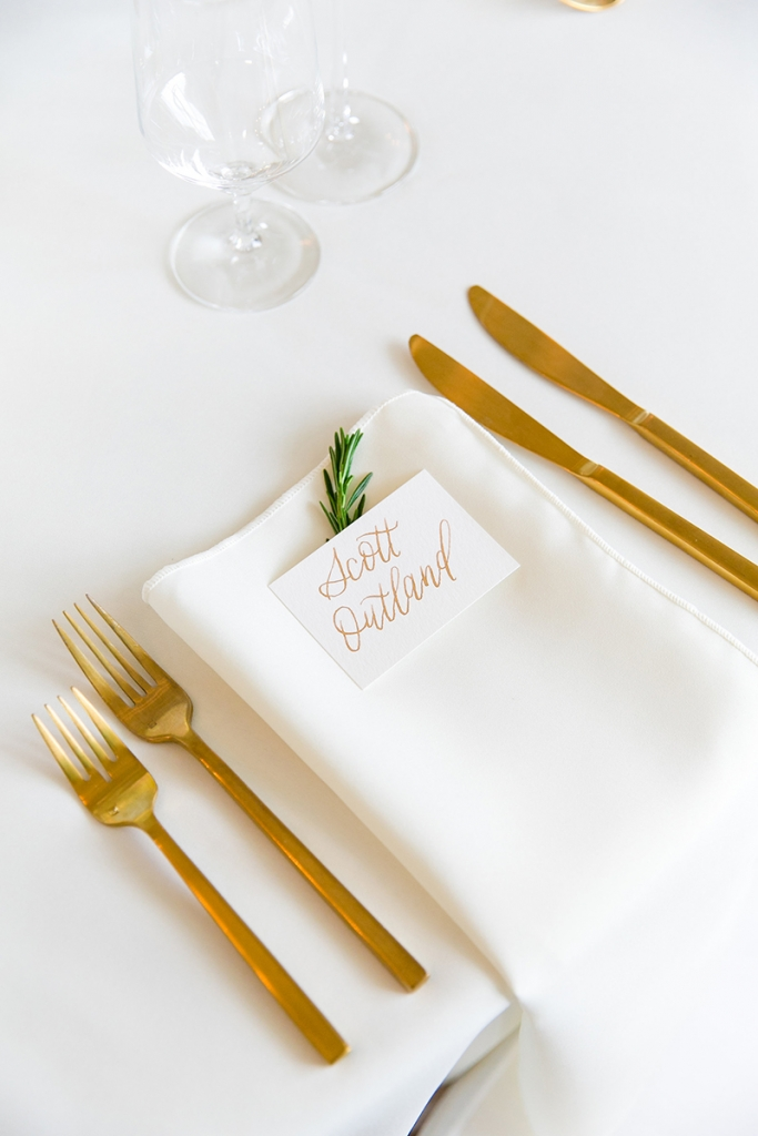 TIP: Stick with one calligrapher. Gold calligraphy (seen here on the invitations and place cards) is as ornate as it gets. Keep the look clean by using the same artist for multiple elements in the metallic hue.  Image by Dana Cubbage Weddings