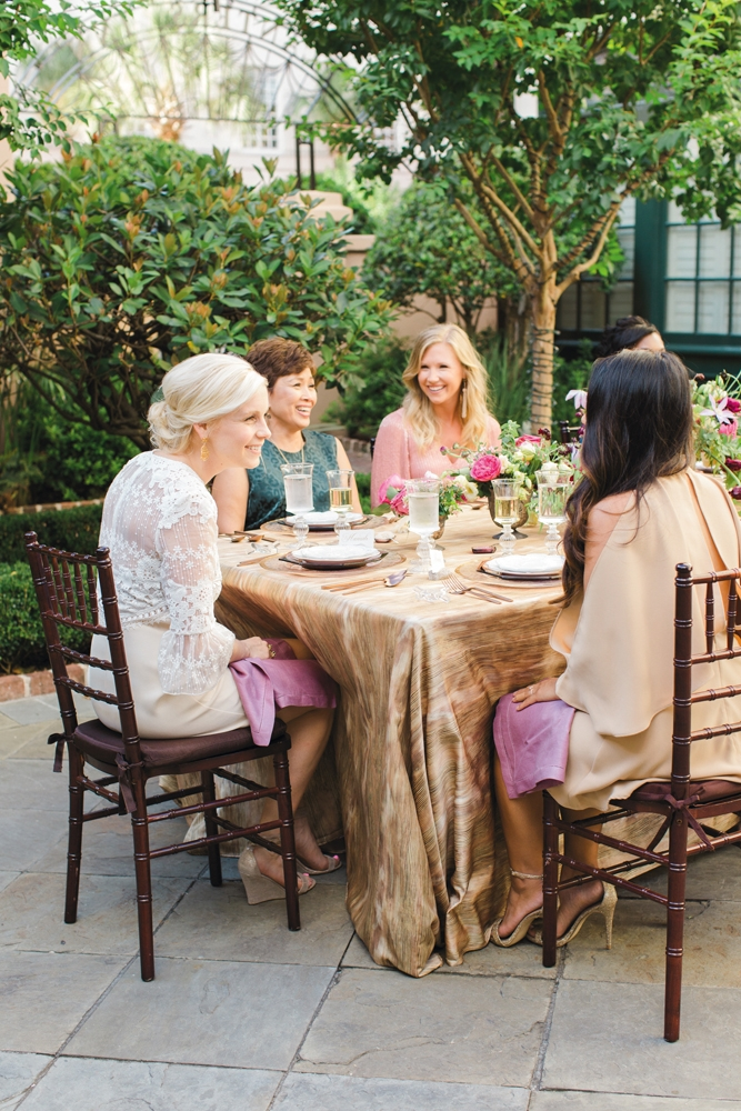 "Smaller gatherings make using formal china more feasible. ""You'd be surprised who may have a fabulous collection and wants to share—like your future mother-in-law,"" says Calder. ""Most of us agree—we don't break it out enough!"" WHAT THEY WORE: ""MOG"" Linda (second from left) in  BCBGMAXAZRIA's ""Sheridan"" dress in  elm from Belk. Molly (third from left) in Alice + Olivia's ""Tammin"" kaftan in dusty rose from Gwynn's of Mount Pleasant; Sara Simpson Design tassel earrings from Bridal House of Charleston. <i>Photograph by Gayle Brooker</i>"