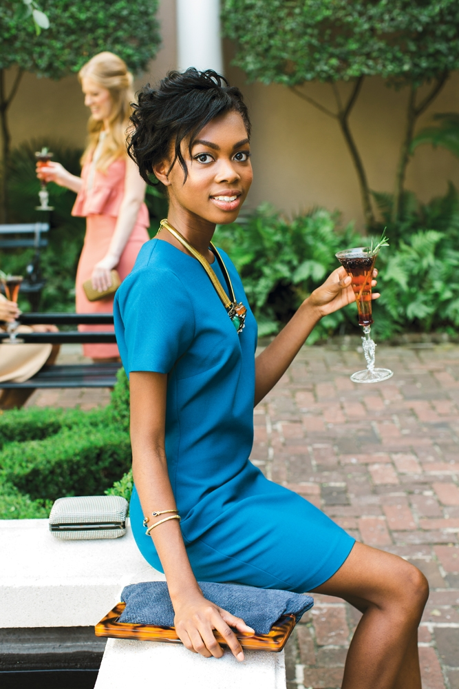 "WHAT SHE WORE: Imani in Likely's knit dress in ""cerulen"" from Copper Penny; Iradj Moini necklace from RTW; gold bangles from Croghan's Jewel Box; ""Harris"" suede clutch in demin from J.McLaughlin. Whiting & David's ""Dimple Mesh Minaudiere"" clutch in pewter from Shoes on King. <i>Photograph by Gayle Brooker</i>"