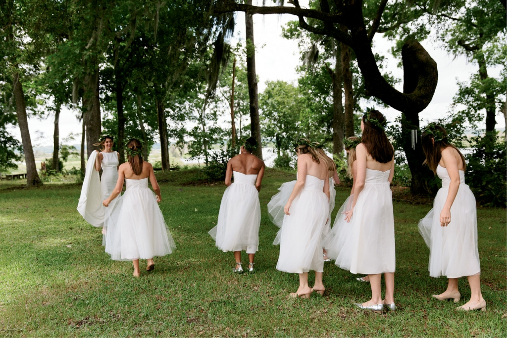 "Bridesmaids wore tea-length white tulle dresses from Alexandra Grecco. ""With their flower crowns, they looked like little nymphs!"" says the bride.  <i>Photograph by Olivia Rae James</i>"