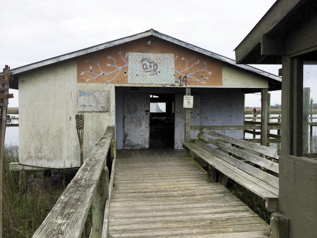 Before: The Bowens Island Dock House, was the one and only potential venue Amelia scouted. Given free rein to freshen up the space, she swept out years of shrimp and oyster shells, washed the windows, and painted the facade from a 10-foot ladder during low tide.   Image by Susan Dean Photography at Bowens Island Restaurant.