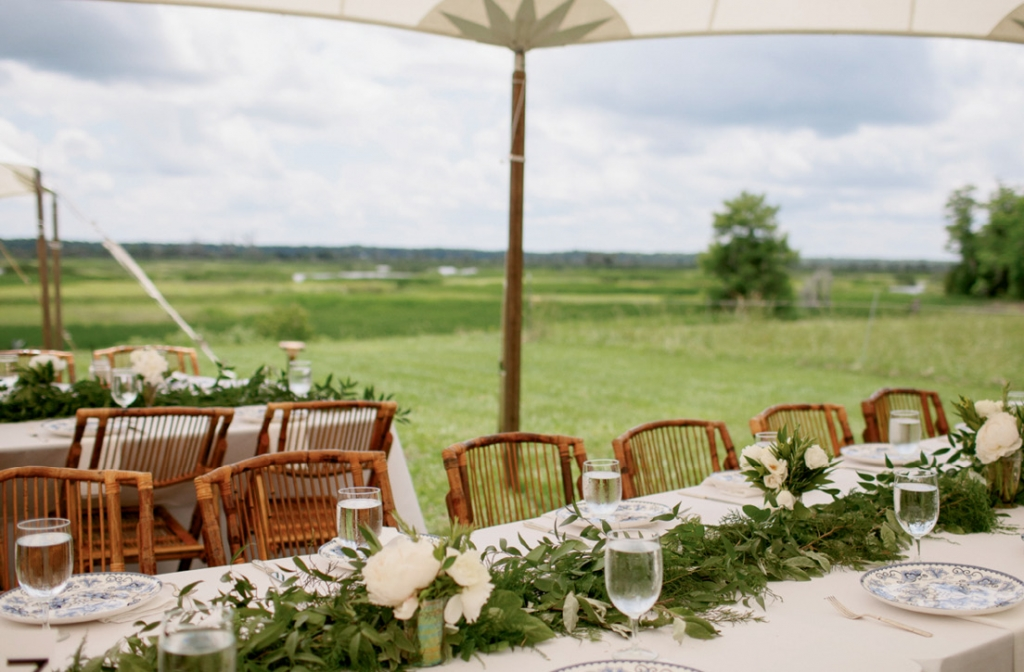 The bride limited the table design to simple garlands and chargers so as not to compete with the natural beauty of the Combahee River.  <i>Photograph by Olivia Rae James</i>