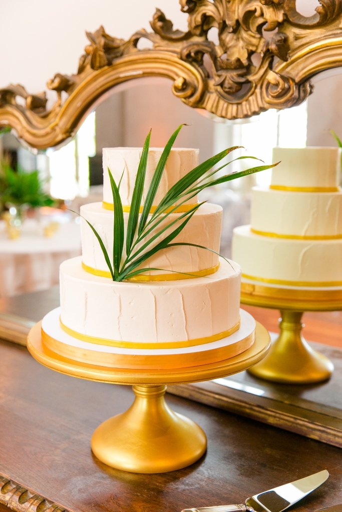 """Mike couldn't make it to our tasting, so DeClare sent us sample cakes for my birthday,"" recalls Kate. Golden bands circling each tier and a single palm frond completed the dessert's modern design. <i>Photograph by Dana Cubbage Weddings</i>"