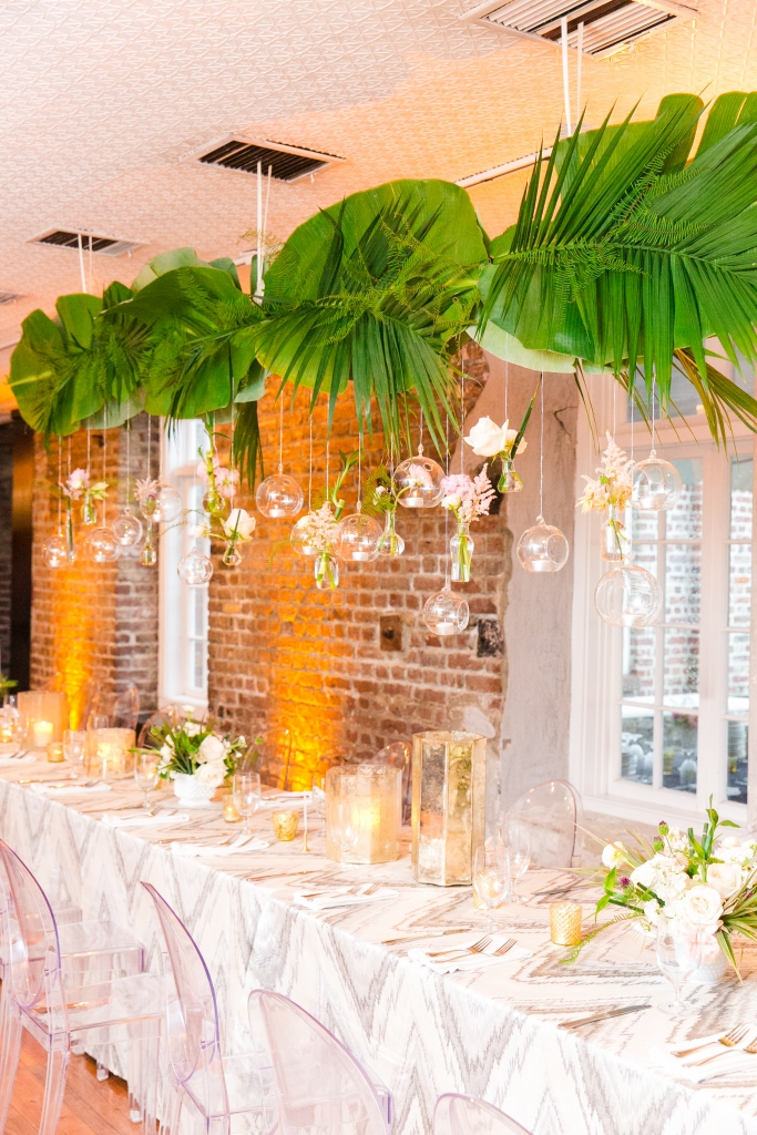Greenery is often more cost-effective than florals, so the overhead installation of palm fronds, banana leaves, and sea star fern was as budget-savvy as it was stunning. <i>Photograph by Dana Cubbage Weddings</i>