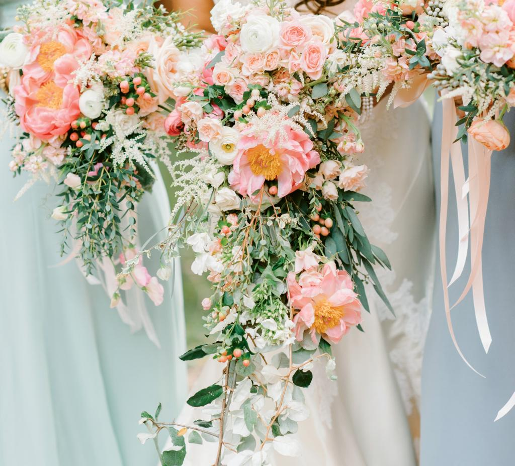 Bride Michelle Carlson opted for a cascading bouquet that almost swept the ground. Her maids of honors' bouquets trailed slightly, and the rest of the attendants carried traditional blooms with trailing ribbons to balance the looks.