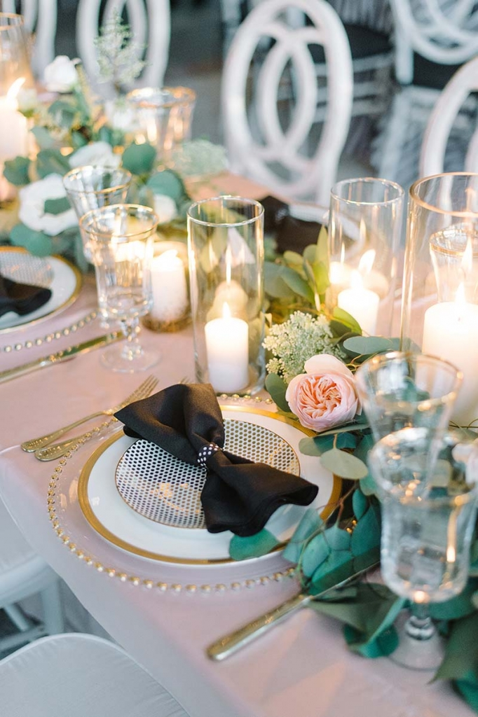 Let the head table make the biggest design statement, like with this dotted salad plate, charger rimmed with golden beads, and bow-tied napkins. <i>Photograph Lauren Jonas</i>