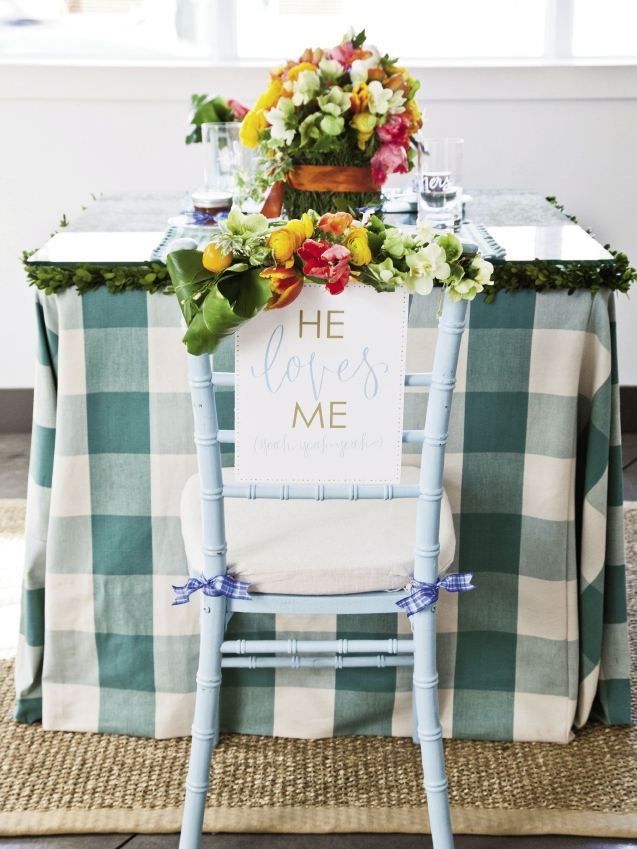 """SIGN OFF: """"He/She Loves Me, yeah, yeah, yeah"""" signs by Hardink Calligraphy and dodeline designs hung on the couple's chairs."""