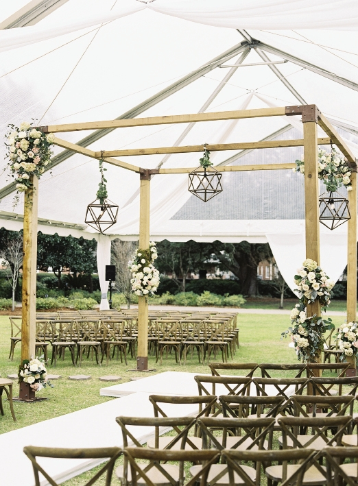 A clear-top tent protected the ceremony site and the custom timber frame altar when the day turned rainy. Laura says she would hang these lanterns throughout her house if there were room.  Rentals from Snyder Events. Lighting by EventHaus. Wedding design by A Charleston Bride. Image by Virgil Bunao Photography at Lowndes Grove Plantation.