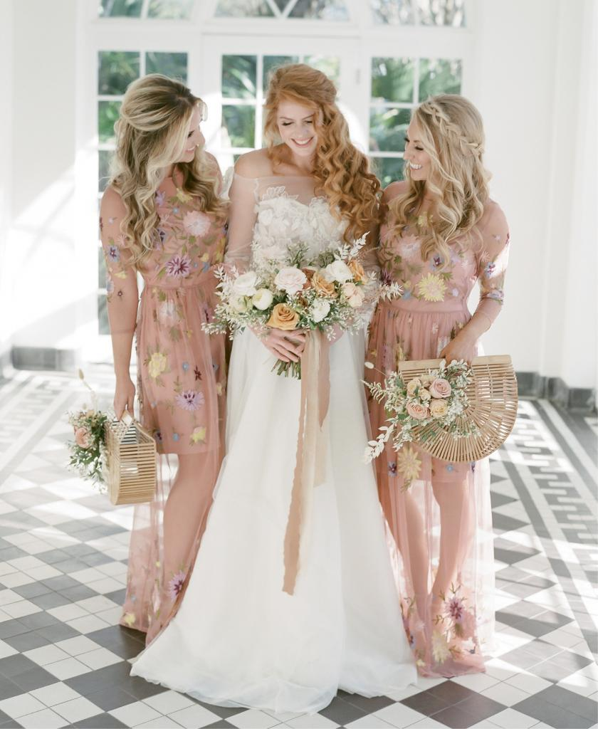 """Inspired by the butterflies in this shoot, designer Emily Kotarski made this custom bridal gown with 3-D lace that flutters in the wind. Florist Andrea Gray Harper added """"a dainty foraged shrub"""" to the hand-held florals for femininity that wasn't """"too girly,"""" as she says. Photographer Justin Brown of The Happy Bloom suggested bridesmaids carry bamboo clutches decked out in flowers"""