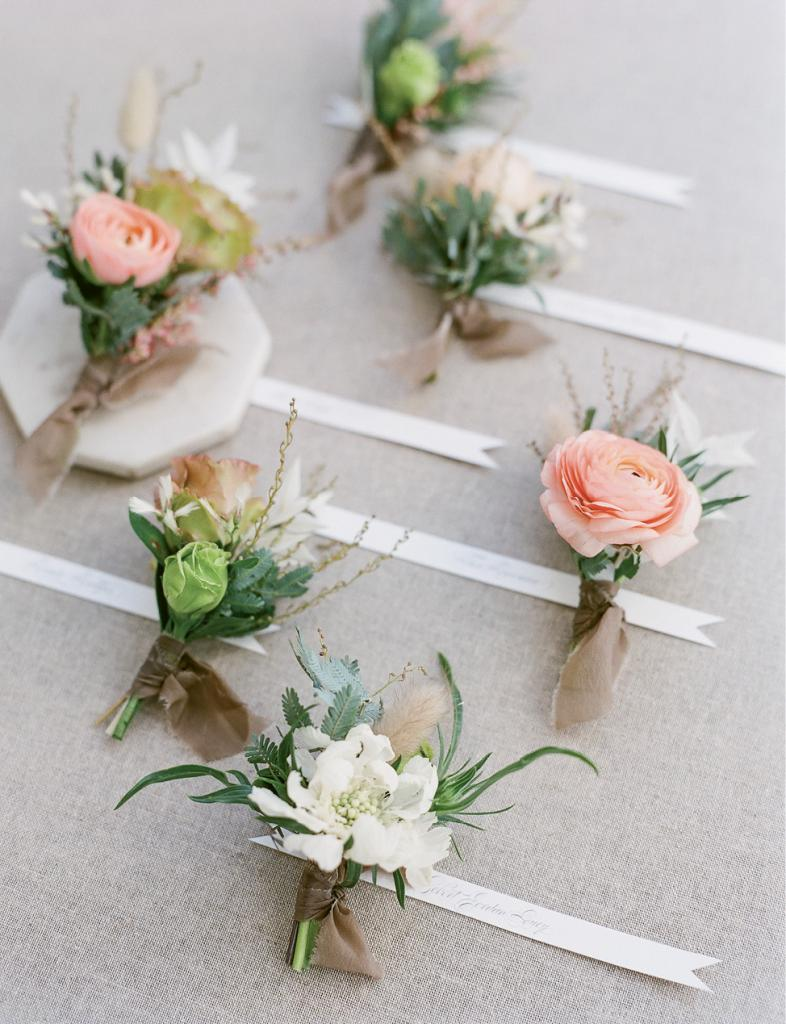Finish boutonnieres with trailing raw silk that harkens the bridal bouquet ribbons.
