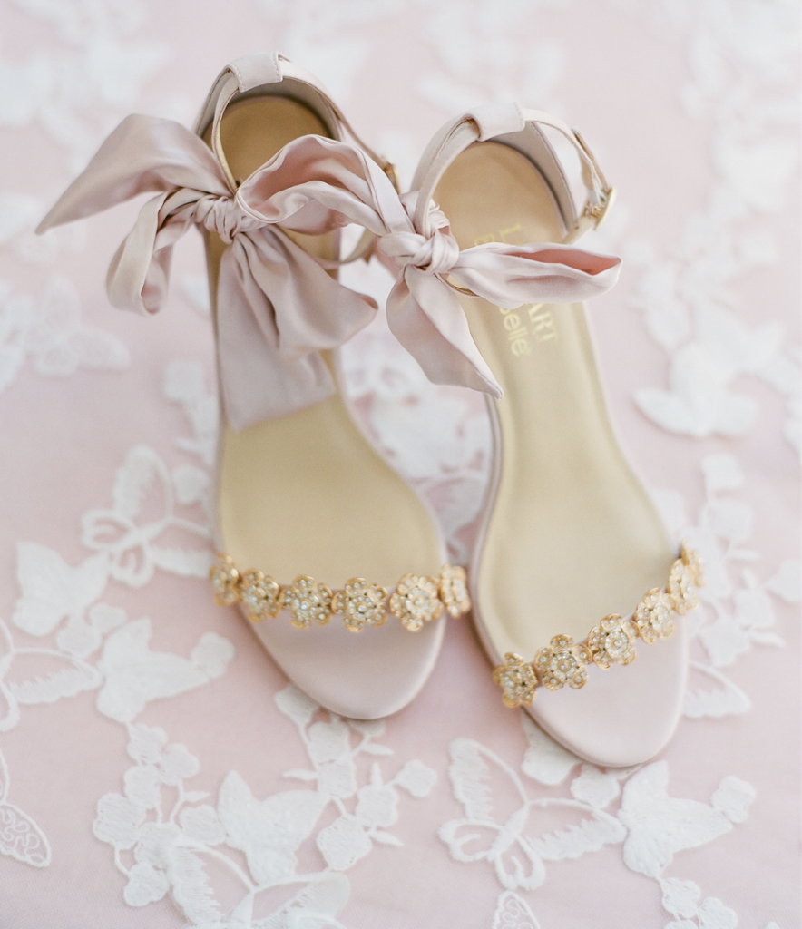 Dainty bloom accents and satin bows at the ankle make these heels spring goddess fare. A fan of flat-lay memento photographs? Share enough yardage of a favorite lace linen with your photographer to use in styled shots, then have a seamstress create table runners or tablecloths from it for your newlywed nest.