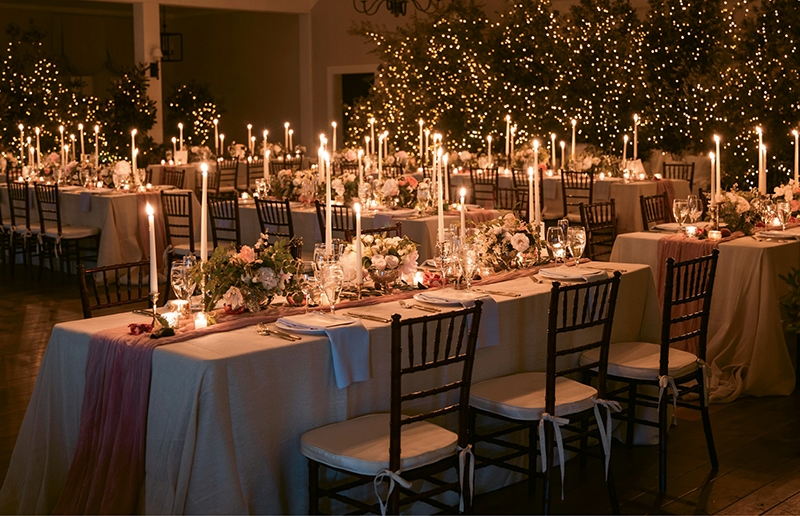 """We wanted to keep it elegant and softly romantic,"" says bride (and interior designer) Lisette of why she and planner Alise skipped hurricane glasses on the tabletops. To generate an intimate, magical feel, they covered rented trees in the tiniest Christmas tree lights they could find. To cap off the ethereal styling, Alise hand-dyed muslin for runners and ran them across simple linen dropcloths.   <i>Photograph by Eric Kelley </i>"