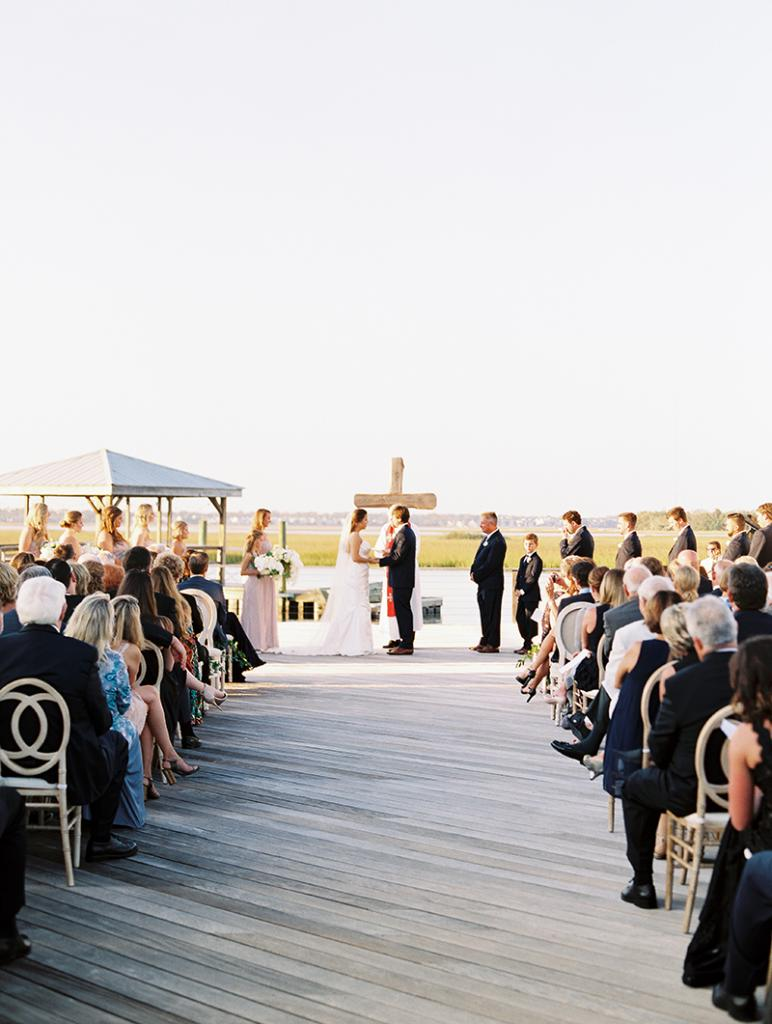 The couple intentionally chose a simple wooden cross for their altar so as not to distract from the view. To up the chic (and comfort) factor, 300-plus cushioned chairs were set out.