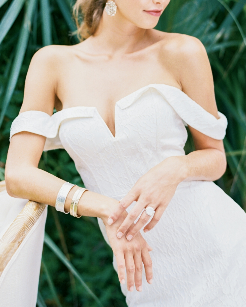 "Rebecca Shoneveld's ""Devon"" corseted fit-to-flare Spanish jacquard gown from Southern Protocol Bridal. Beaded drop earrings from Copper Penny. Bracelets from Out of Hand. Jude Frances's moonstone and diamond ring from Croghan's  Jewel Box. Chair from Ooh! Events. Location: Seabrook Island Lake House, Pond Trail. Photograph by Perry Vaile"