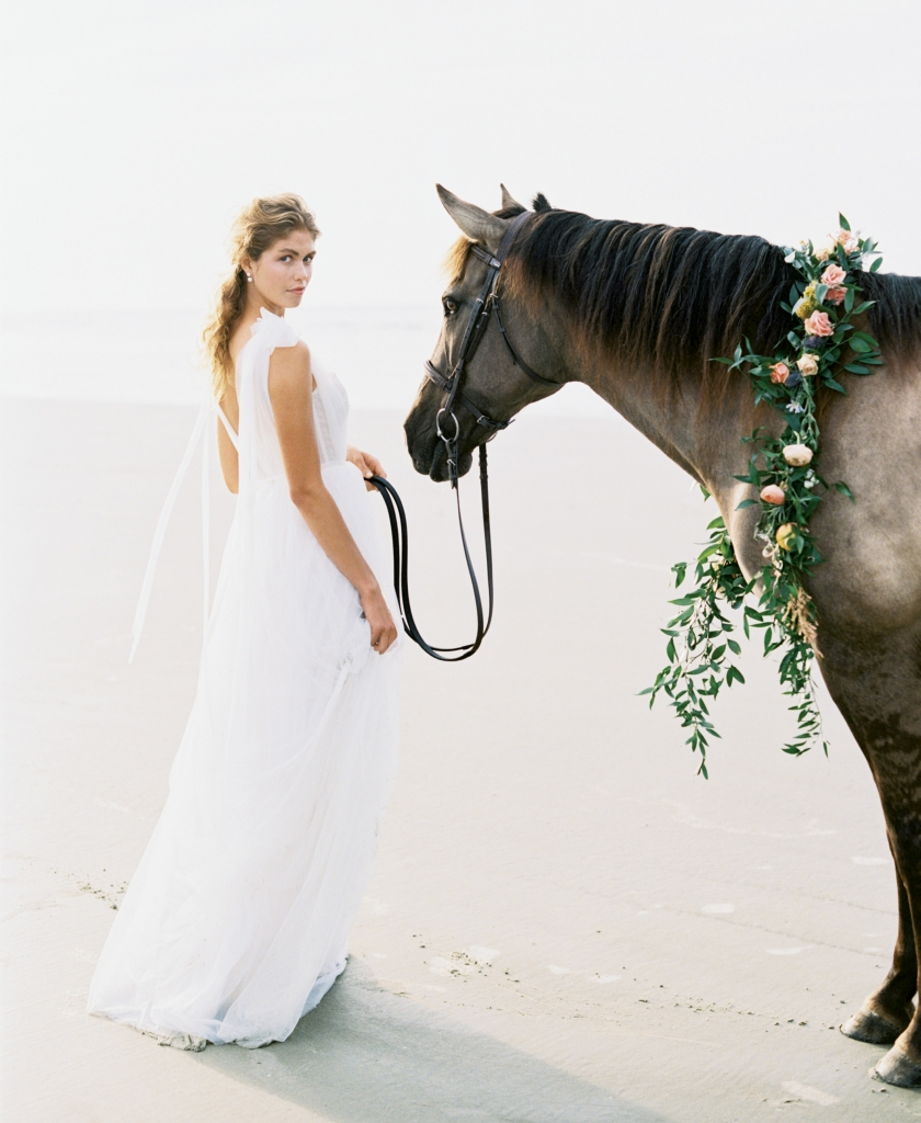 """Kendall"" corseted tulle gown with pearl accents by Emily Kotarski Bridal. Pearl jacket earrings from Southern Protocol Bridal. Carolina Marsh Tacky pony, ""Silky"", from Seabrook Island Club Equestrian Center. Florals by Out of the Garden. Location: Seabrook Island, Beach Access 6.  Photograph by Perry Vaile"