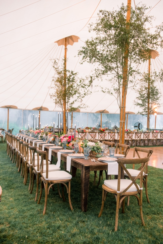 """The tent was gorgeous, but very tall,"" says florist Anne. ""Adding oak branches to the poles made the space more intimate."" <i>Image by Timwill Photography</i>"